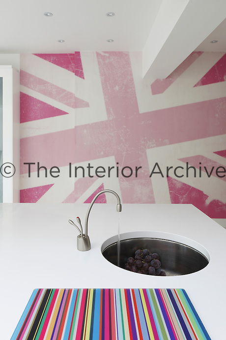 A bright pink Union Jack wallpaper adds colour and interest to the sleek white kitchen