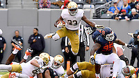 Irish running back Josh Adams (33) leaps over defenders in the fourth quarter.