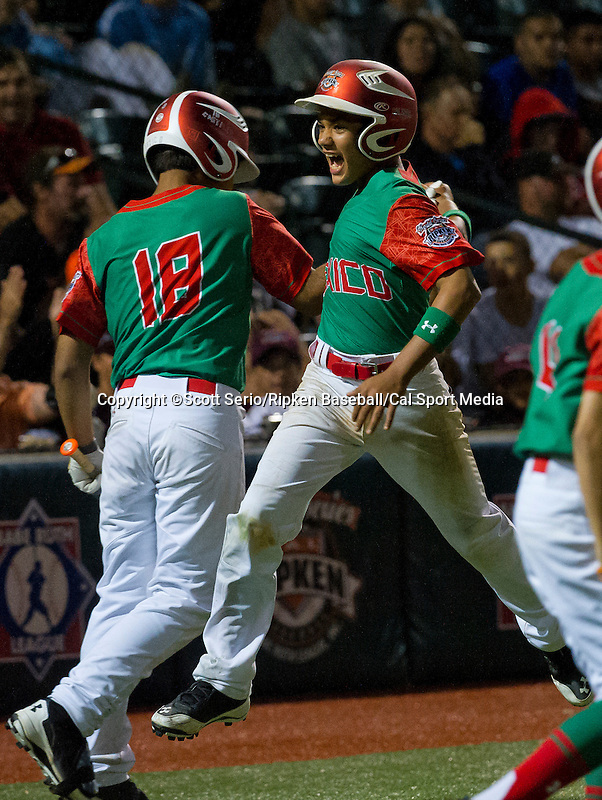 August 15, 2014: Mexico's Jesus Castillo (18) congratulates team-mate after home run against Japan during the Cal Ripken 12u 70-foot World Series United States Championship at the Ripken Experience powered by Under Armour in Aberdeen, Maryland on August 15, 2014, Mexico won 10-7.Scott Serio/Ripken Baseball/CSM