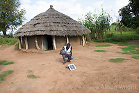 N. Uganda, Kitgum District. Young man powering light in his home with a solar panel.