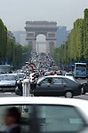 Traffic moving along the Champs Élysées in Paris. With the Arc de Triomphe in the background.