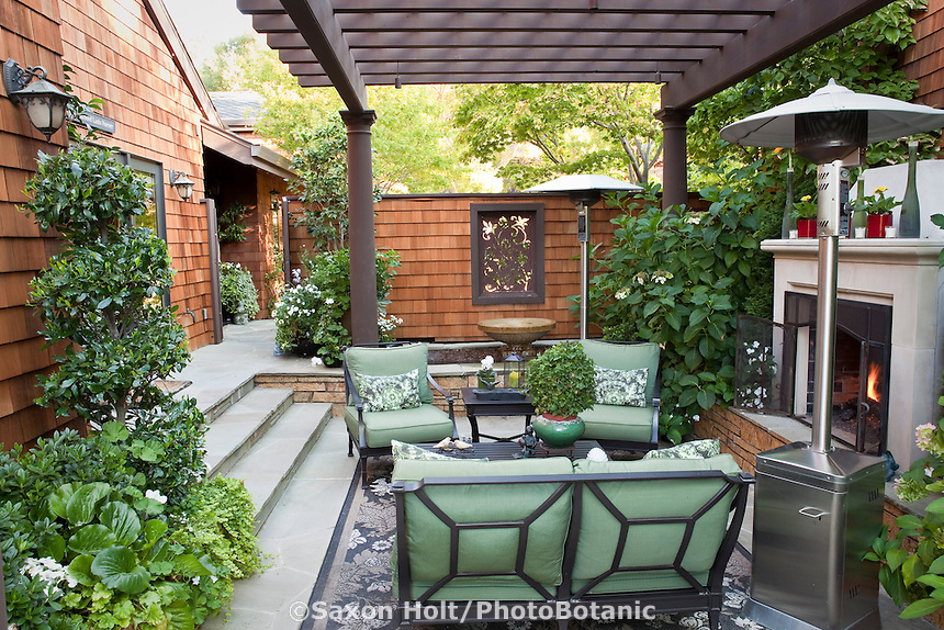 Small space urban patio garden room sunken between town home walls and covered by pergola