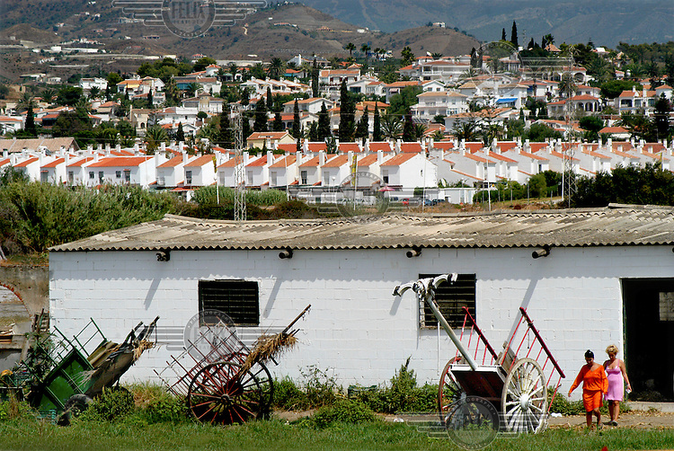 Hay carts next to a 'cortijo' (a typical Andalusian house). In the background, new housing constructed as part of the rapid urbanization of the Spanish coast.