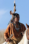 A Native American Indian man on horseback scouting for enemies with a stone mallot weapon in the prairie of South Dakota