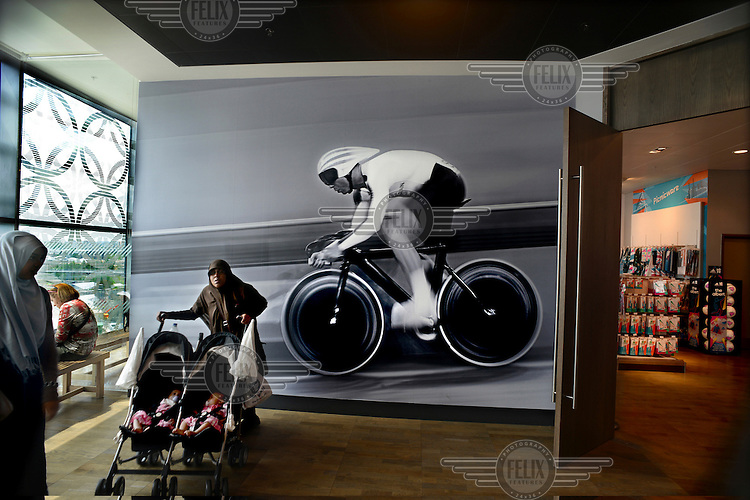 A Muslim woman pushes a double baby buggy past a giant photograph of a track cyclist beside an Olympic 2012 merchandise shop. The shop is in the Westfield Centre, Europe's biggest shopping mall that is next to the Olympic Park, in Stratford, East London.