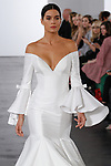 Model walks runway in an off-the-shoulder v-neck dropped waist mermaid bridal gown with tiered skirt, from the Dennis Basso for Kleinfeld 2018 Bridal Collection on October 5 2017, during New York Bridal Fashion Week.