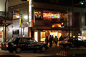 Patrons leaving a Kyoto restaurant, milling around before departing by taxi.