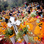 Mexican people gather around the graves, covered by marigold flowers, honouring their deceased relatives during the ritual celebration of the Day of the Dead (Día de Muertos) at the cemetery of Tzurumútaro, Michoacán, Mexico, 2 November 2014.