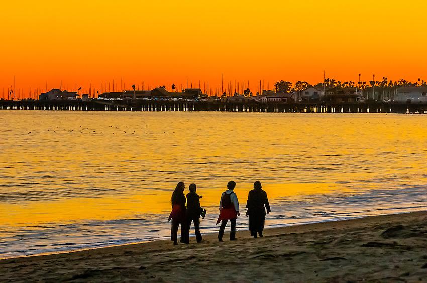 People walking on East Beach at sunset (with Stearns Wharf behind), Santa Barbara, California USA.