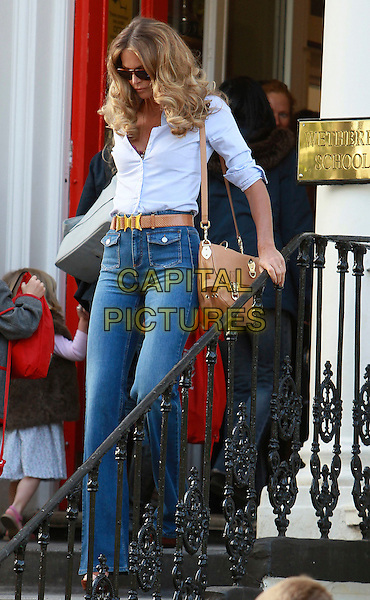ELLE MACPHERSON.Pictured on the School Run in central London, England, UK,.April 27th 2011..full length wide leg denim jeans 70s seventies curly hair shirt white blue belt tan brown high waisted platform shoes high heels sandals sign Wetherby pockets ray bans sunglasses bag satchel mulberry walking down steps .CAP/HIL.©John Hillcoat/Capital Pictures