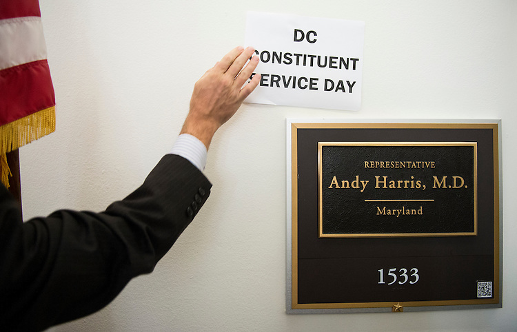 "UNITED STATES - JULY 24: James Jones, communications director for DC Vote, tapes a ""DC Constituents Service Day"" sign on the wall as he stands with other DC residents outside of Rep. Andy Harris's office on Capitol Hill to protest Harris' actions against D.C.'s marijuana laws on Thursday, July 24, 2014. DC Vote encouraged DC residents to bring their complaints about city services to the Maryland congressman. (Photo By Bill Clark/CQ Roll Call)"