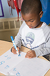 Education Preschool 3-4 year olds boy writing numbers in notebook using marker