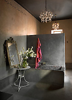 Marrakech interior designer Marie-Christine Nourry turns riads into lofts.  Here she has created an open plan bathroom illuminated with crystal chandeliers and furnished with a concrete bath decorated in hand-made mosaic tiles