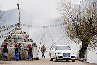 CHINA Provinz Yunnan , Audi Automobil und Mosuo Frauen umrunden einen buddhistischem Schrein am Lugu See, hier lebt die ethnische Minderheit der Mosuo  , die Mosuo sind Buddhisten und Mosuo Frauen ueben ein Matriarchat aus / CHINA province Yunnan, Lugu Lake , Audi car and Mosuo women at buddhist shrine, the ethnic minority Mosuo are buddhist and women have a matriarch
