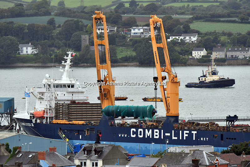 Pictured: 200 ton column being loaded onto giant heavy lift ship at Pembroke Dock, Wales, UK<br /> Re: A large dismantled section of an oil refinery has been taken away by road ready to be shipped and rebuilt in Pakistan.<br /> Policing units escorted it on the five-hour journey from the former Murco site in Milford Haven, Pembrokeshire, to Gelliswick Bay on Tuesday.<br /> About 600 people once worked there but it closed in November 2014.<br /> It is now a storage facility, with about 100 people carrying out decommissioning work over two years.<br /> The load will remain on the beach overnight before being taken away by barge on 6 September.<br /> Decommissioning is set to be completed in Autumn 2018, with the whole refinery being re-assembled in Pakistan.