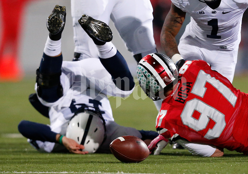 Penn State Nittany Lions quarterback Christian Hackenberg (14) is tackled by Ohio State Buckeyes defensive lineman Joey Bosa (97) during Saturday's NCAA Division I football game at Ohio Stadium on October 26, 2013. (Barbara J. Perenic/The Columbus Dispatch)