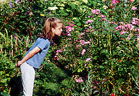 Girl smelling flowers in garden.