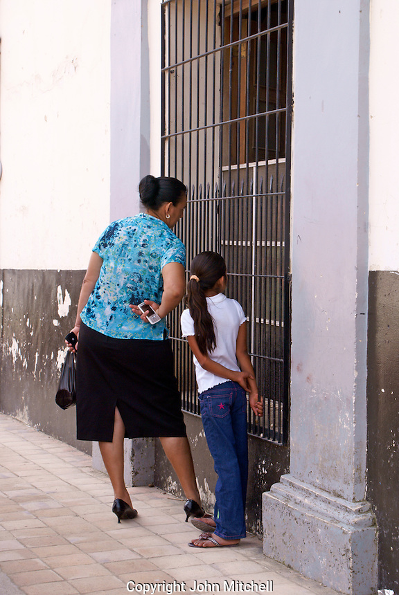 Woman holding cell phone with young girl in the Spanish colonial town of Gracias, Lempira, Honduras...