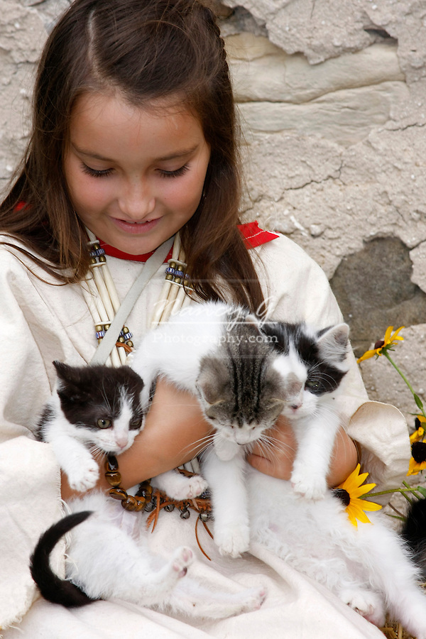 A Native American Indian girl holding three kittens