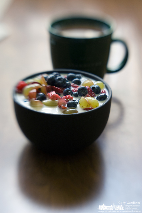 A breakfast bowl of cereal with strawberries, raspberries, blueberries, and grapes sit with a cup of coffee on a table with a newspaper.<br />