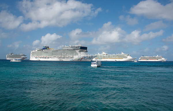 Four large cruise ships, from left to right, the the P&amp;O Azura, which carries 3,100 Passengers and 1,250 Crew; the Norwegian Epic, which carries 4,100 passengers and 1,724 crew; the Royal Caribbean Freedom of the Seas, which carries 4,515 passengers and 1,360 crew, and the Celebrity Reflection, which carries 3,609 passengers and 1271 crew, are lined up in the harbor of George Town, Grand Cayman in the Cayman Islands on Tuesday, December 20, 2016.  The smaller boats are tenders to ferry passengers back and forth to the island.<br /> Credit: Ron Sachs / CNP /MediaPunch