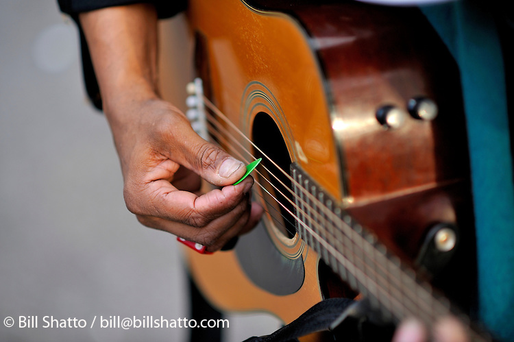 A close-up of a man's hand playing a guitar in New York City's Washington Square Park.