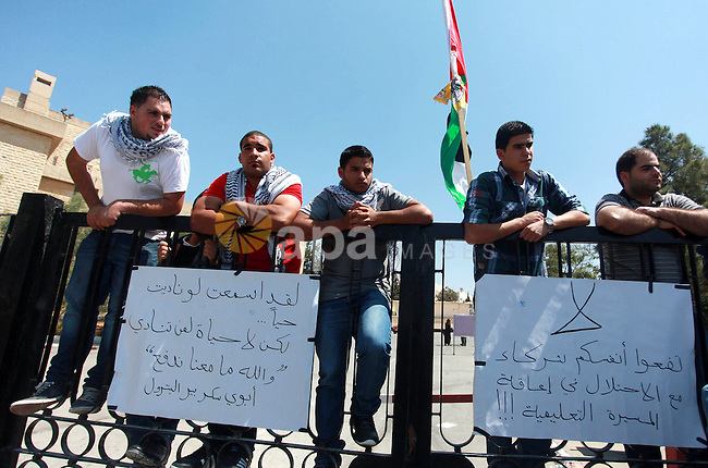 Palestinian students of Birzeit University stand on the gate of their University as they protest against rising of the tuition fees, near the West Bank City Ramallah, 02 September 2013. Photo by Issam Rimawi