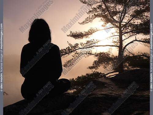 Silhouette of a woman sitting on rocks and facing sunrise sun, tranquil nature scenery, relaxation and meditation spiritual concept