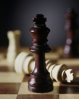 Brown and white wood chess pieces and board, the king chess piece.