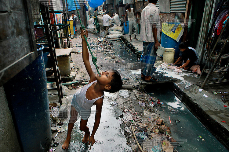 A boy playing among the sewers and recyclers. The waste recycling industry is helping thousands of slum dwellers out of poverty. The recycling of the discarded waste of Mumbai's 19 million citizens is a thriving business propelled by thousands of micro entrepreneurs. Economists estimate that the output of the slum is over 1 billion USD a year.