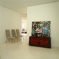 A painting incorporating the American flag rests on a chest and three chairs fashioned out of glass jars furnish the entrance hall of this loft apartment