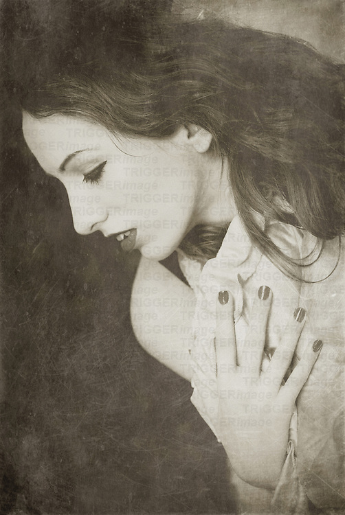 a monochrome portrait of lady holding one hand on her chest in profile