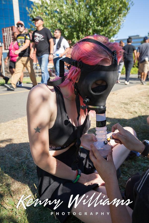 Girl smoking weed in her bong gas mask, Hempfest Seattle, WA, USA.