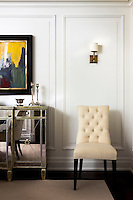 A button-back chair is placed beside a mirrored sideboard set against the panelled wall of the living room
