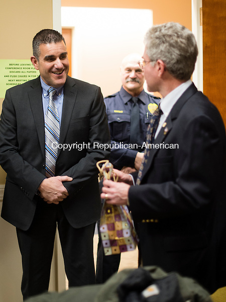 MIDDLEBURY, CT- 11 January 2015-011116EC02-    Middlebury's police chief, James Viadero, is leaving for a chief's job in Newtown. Kenneth Heidkamp, the Chairman of the Police Commission, gives a gift to Viadero Monday night at Middlebury Town Hall. Erin Covey Republican-American