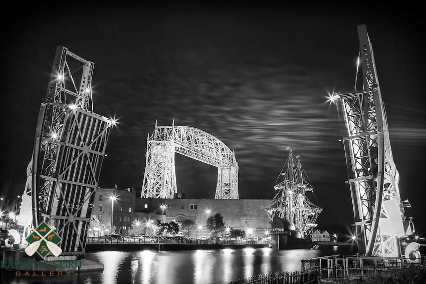 &quot;Duluth Harbor Night Lights&quot;<br /> This night visit to the harbor was filled with radiance and nostalgia. It was the final night the Spanish tall ship, El Gale&oacute;n Andaluc&iacute;a, would spend in Duluth before its departure. The flags fluttered in the warm breeze while the waters lapped at the hull of the ship at rest. The incoming blanket of clouds added welcome texture and mood to the sky.