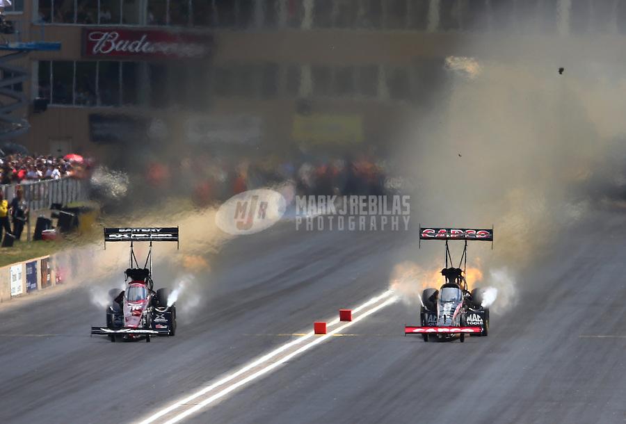 Jul. 20, 2013; Morrison, CO, USA: NHRA top fuel dragster driver Steve Torrence (right) has engine problems racing alongside Spencer Massey during qualifying for the Mile High Nationals at Bandimere Speedway. Mandatory Credit: Mark J. Rebilas-