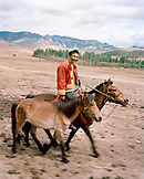 MONGOLIA, Gorkhi-Terelj National Park, a man on horseback leads a horse to his farm and home