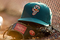 A Greensboro Grasshoppers cap sits on top of the glove of Chris Wade #32 at  L.P. Frans Stadium July 10, 2010, in Hickory, North Carolina.  Photo by Brian Westerholt / Four Seam Images