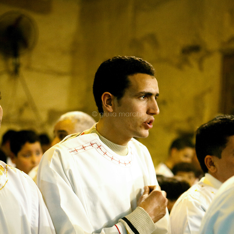 Egypt / Cairo / 6.1.2013 / Altar boys during the Coptic Christmas celebrations at a cave chapel. The chapel is part of the Simon the Tanner Monastery, hidden in a cave in the Mokattam hills, above Cairo's Manshiyet Nasser (also known as Garbage City, Zabbaleen's settlement). © Giulia Marchi