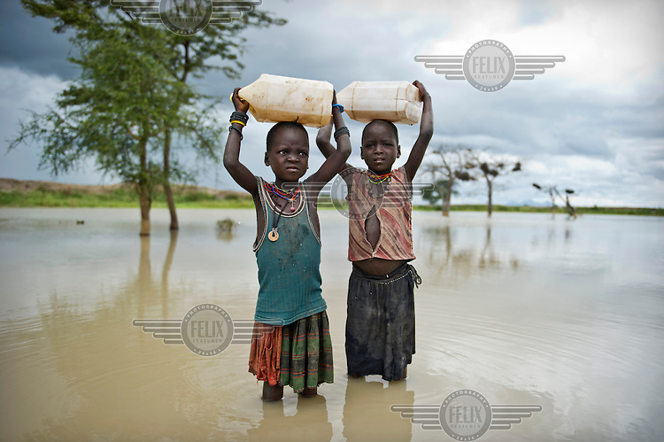 Lotimo Abram (left) and Lokong Apaalokorwo collect drinking water from a rain water dam.
