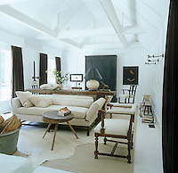 In the living room the antique nail-studded armchair and large comfortable sofa are covered in a matching cream linen