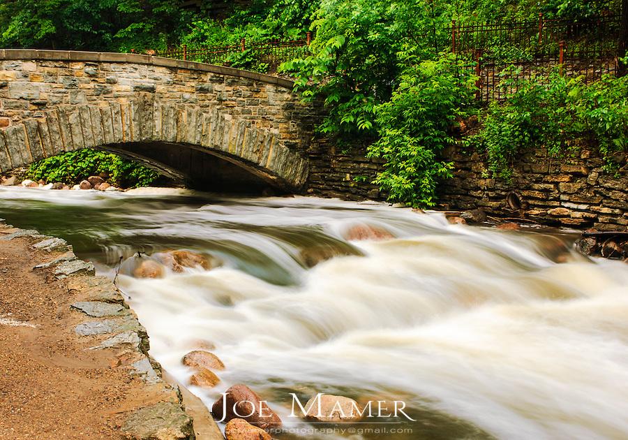 Minnehaha Creek downstream of the falls flowing under a walking bridge.