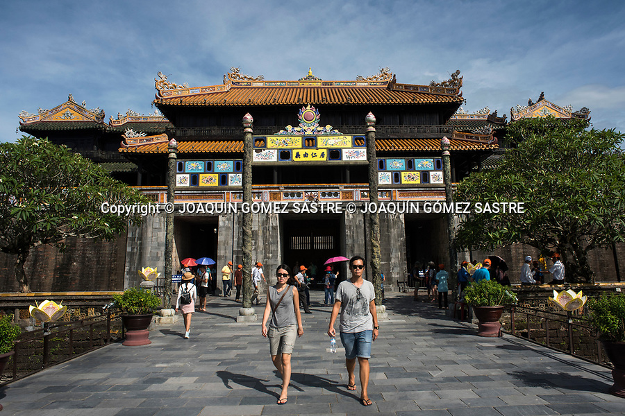 A group of tourists walking through the door of the noon in the Citadel of Hue, inspired by the Forbidden City of Beijing, is a must for any traveler, more if you move through this ancient imperial city of central Vietnam. Was declared a World Heritage Site by UNESCO in 1993<br /> HUE-VIETNAM