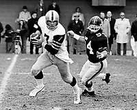 Don Jonas HamiltonTiger Cats quarterback is chased by Jerry Campbell Ottawa Rough Riders 1975. Copyright photograph Scott Grant