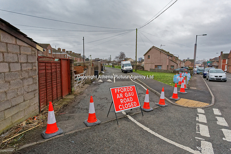 """Pictured: The road has been closed off for traffic leading to the Banksy graffiti on a garage in Port Talbot, Wales, UK. Tuesday 25 December 2018<br /> Re: The artist Banksy has confirmed that a new graffiti piece that has appeared in Port Talbot, south Wales is his.<br /> He announced on Instagram: """"Season's greetings"""" - with a video of the artwork in the Taibach area of Port Talbot.<br /> The image appears on two sides of a garage in a lane near Caradog Street, depicting a child enjoying snow falling - the other side reveals it is a fire emitting ash.<br /> The owner of the garage said he had not slept over fears it might be vandalised."""