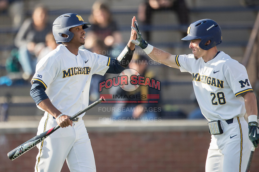 Michigan Wolverines outfielder Johnny Slater (25) is greeted by teammate Nick Poirier (28) after scoring against the Central Michigan Chippewas on May 9, 2017 at Ray Fisher Stadium in Ann Arbor, Michigan. Michigan defeated Central Michigan 4-2. (Andrew Woolley/Four Seam Images)