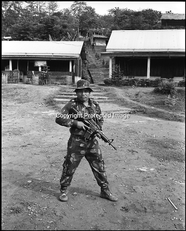 38 year commandant of the Mibang camp, Major Dara Singh poses for a portrait with an M16 assault rifle at the Basabari camp of the ceasefire terrorist group Dima Halim Daoga (DHD) in Mibang in North Cachar hills of Assam, India.