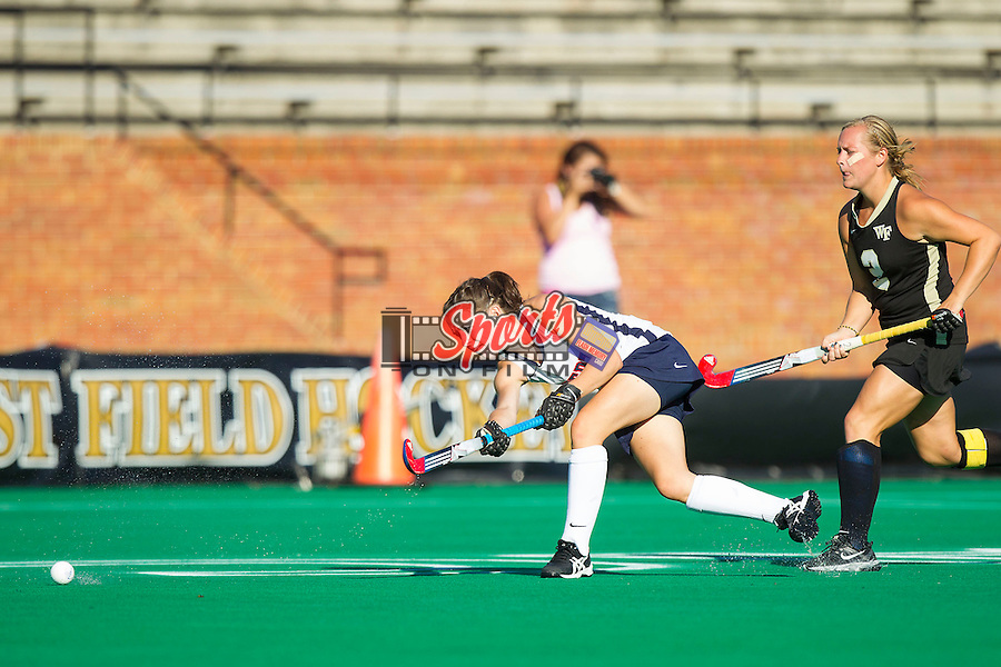 Bethany Barr (12) of the Liberty Flames passes the ball away from the pursuit of Taylor Rhea (2) of the Wake Forest Demon Deacons at Kentner Stadium on September 13, 2013 in Winston-Salem, North Carolina.  The Demon Deacons defeated the Flames 3-2.  (Brian Westerholt/Sports On Film)