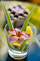 A small glass contains a fresh flower